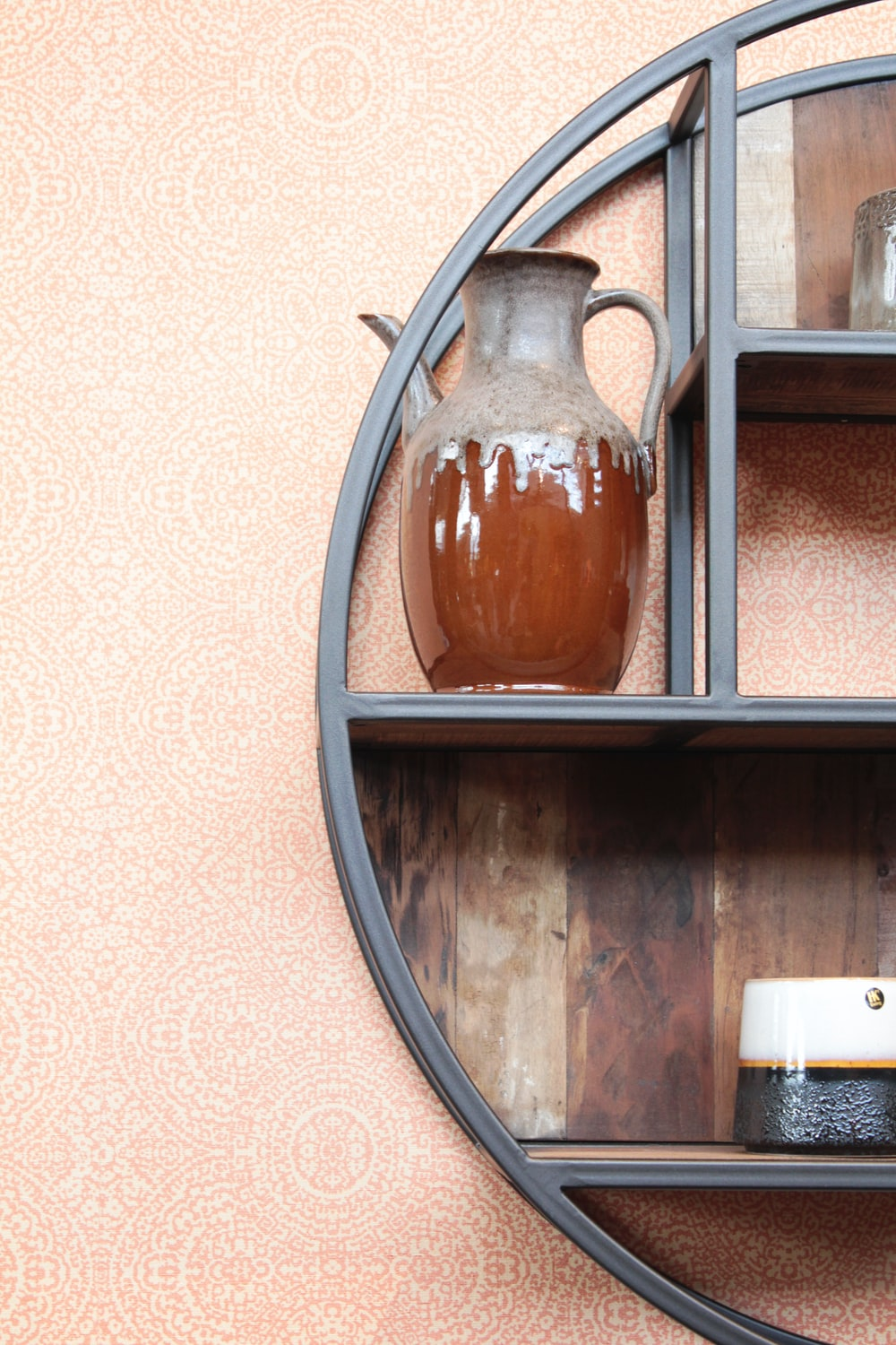 brown and gray ceramic pitcher on black wooden shelf