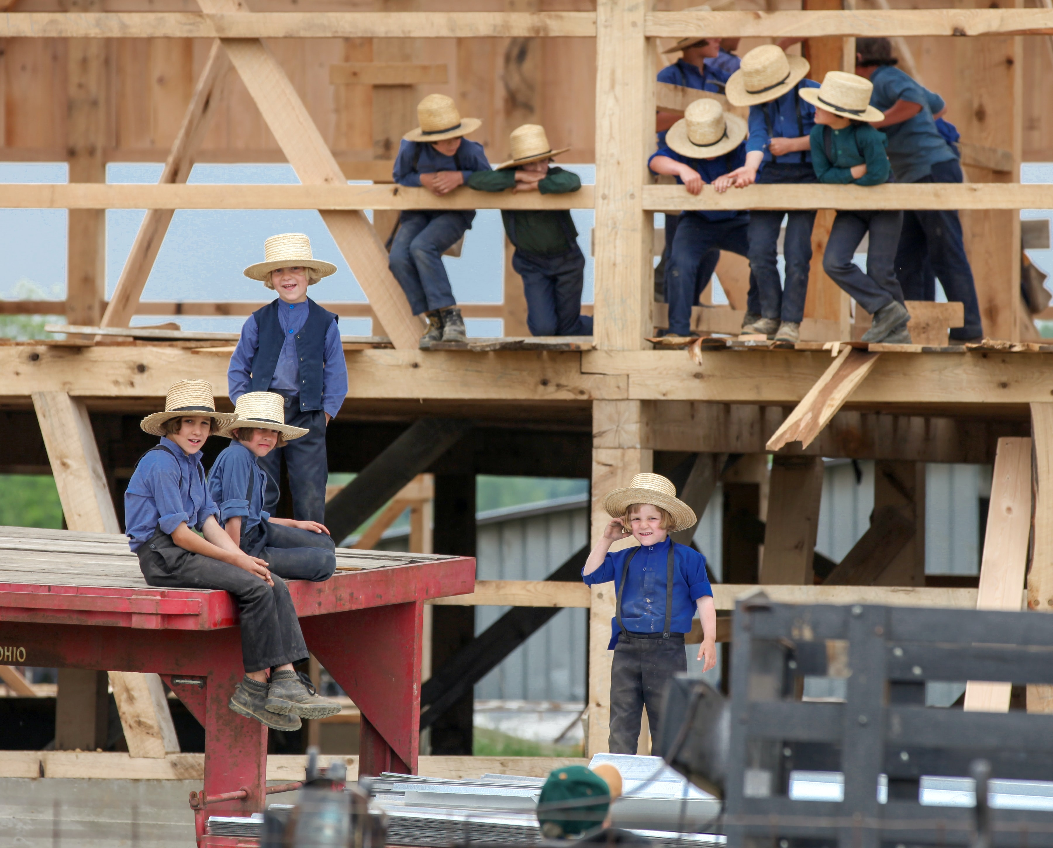 group of children wearing blue shirts and pants climbing on wood during daytime