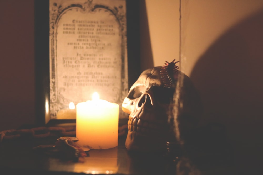 lighted candle beside skull