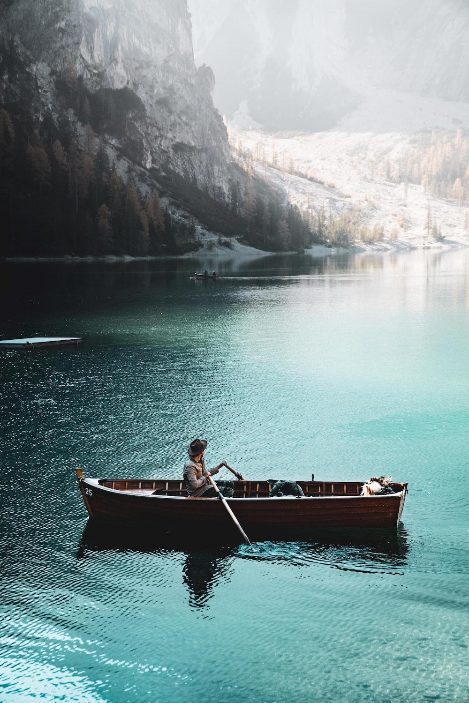 person on boat near mountain range
