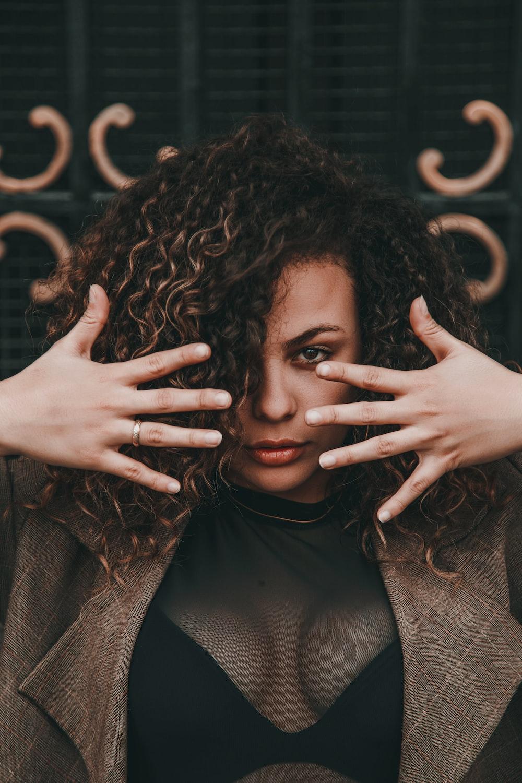 selective focus portrait photo of woman wearing brown suit jacket