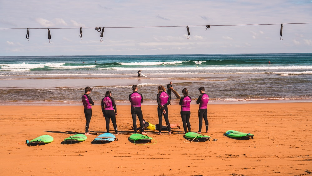 six person in purple-and-black swimming uniforms standing in front of surfboards on shore