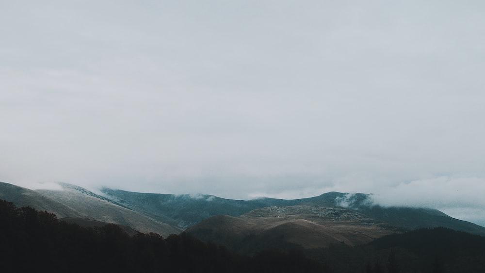 brown mountain under grey clouds