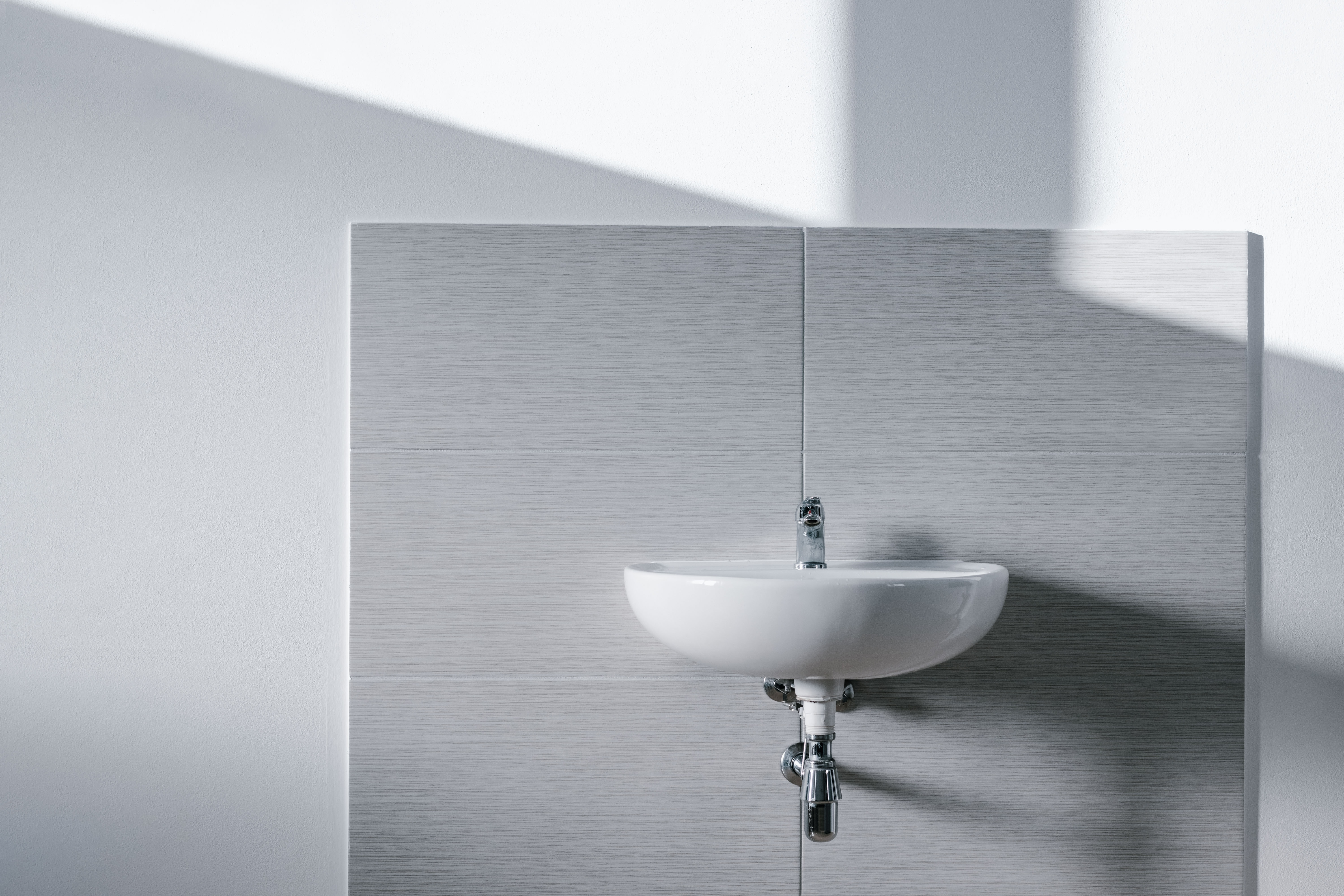 white sink mounted on wall