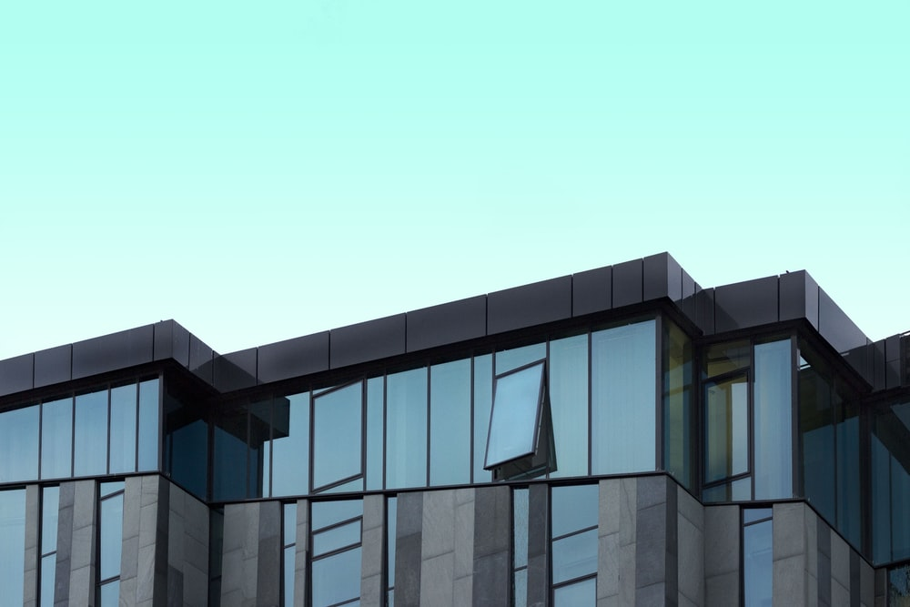 gray and blue curtain wall building under blue sky