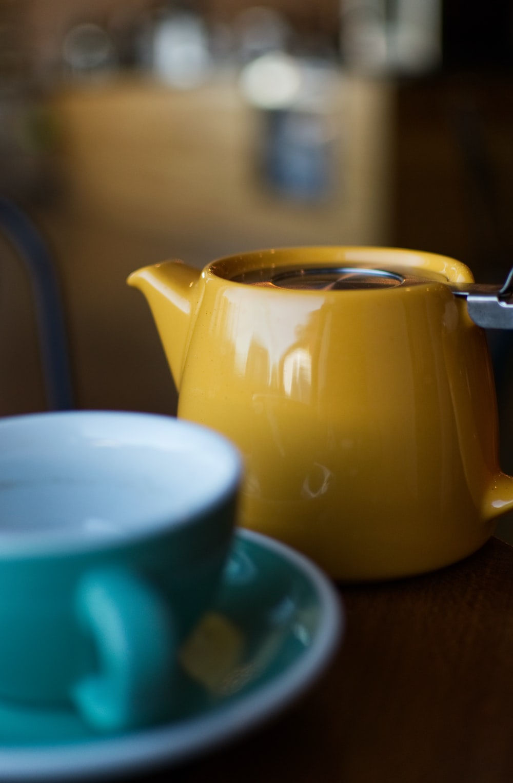 shallow focus photography of yellow ceramic teapot