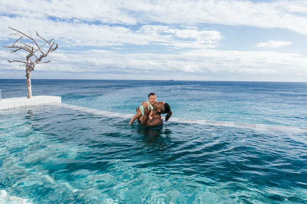 man carrying baby while standing on infinity pool