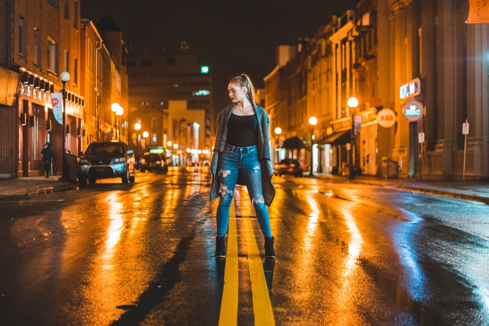 woman standing in middle of road during night time