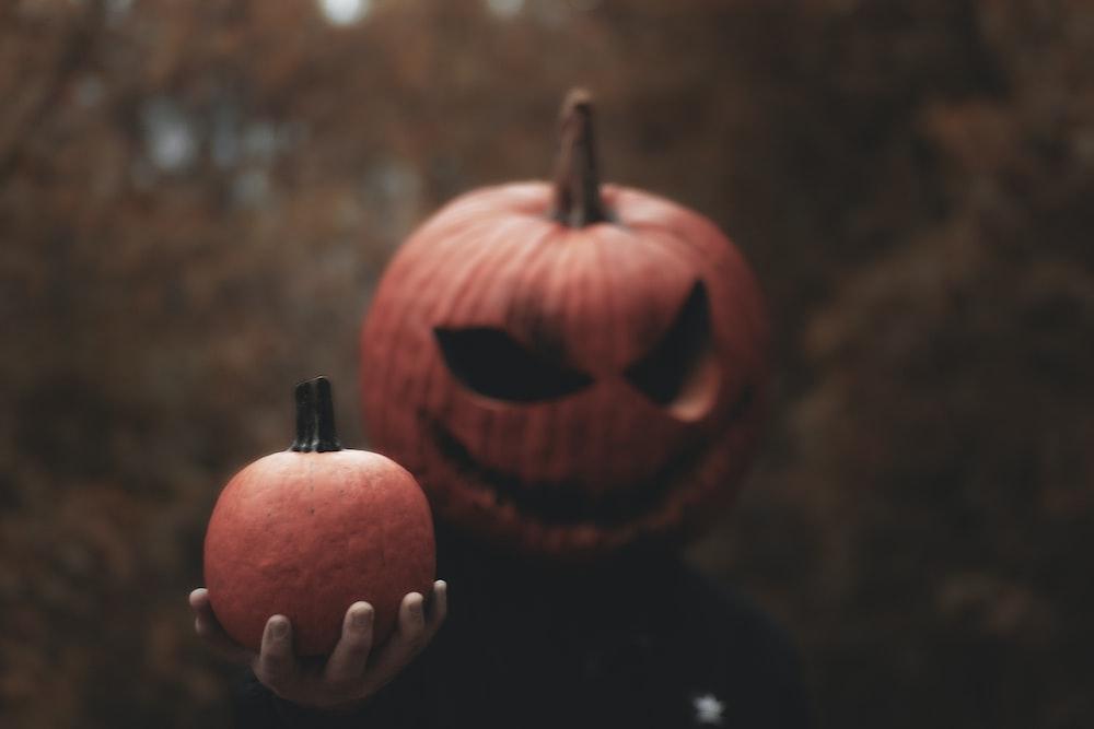 person wearing Jack-O-Lantern mask holding pumpkin