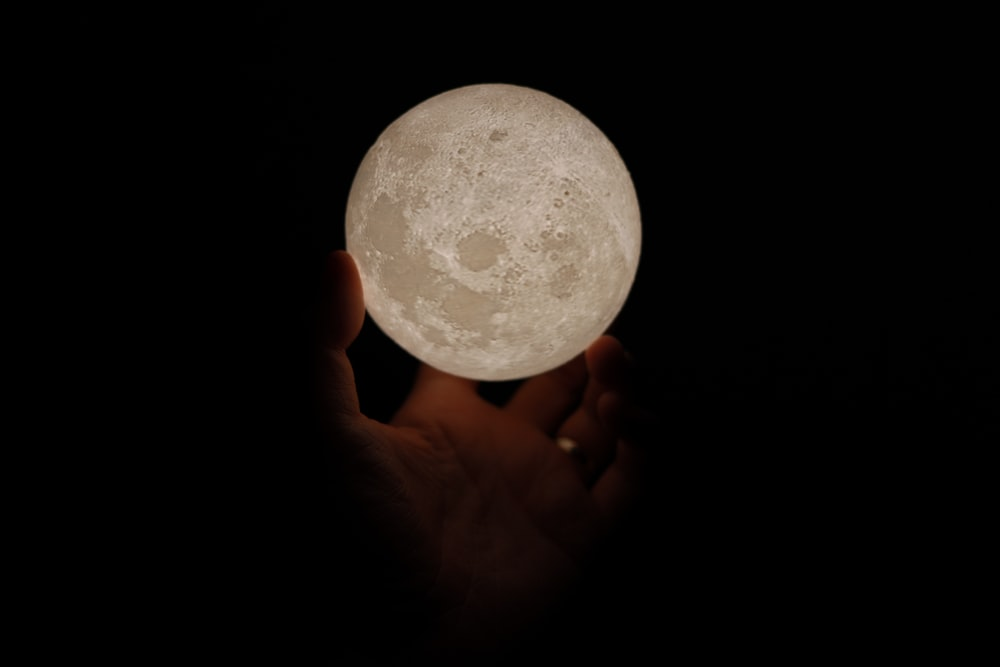person holding white moon lamp