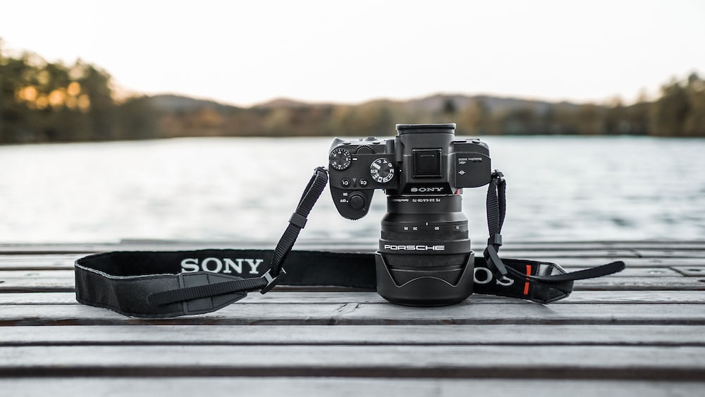 black Sony camera face down on panel by body of water