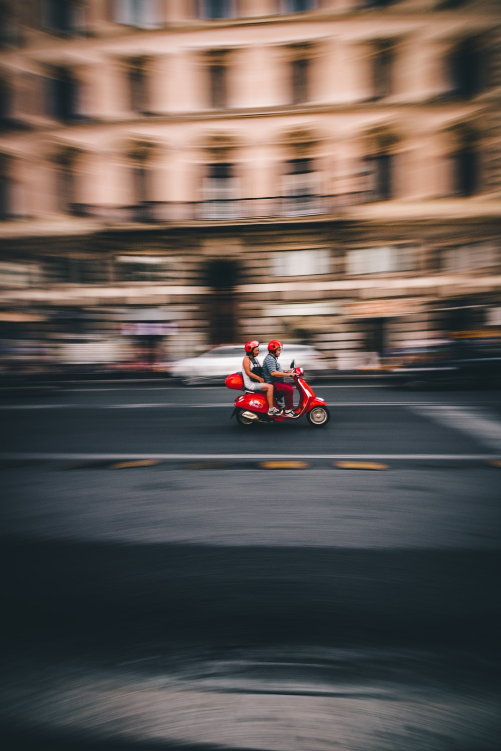 panning photography of two person riding red motor scooter