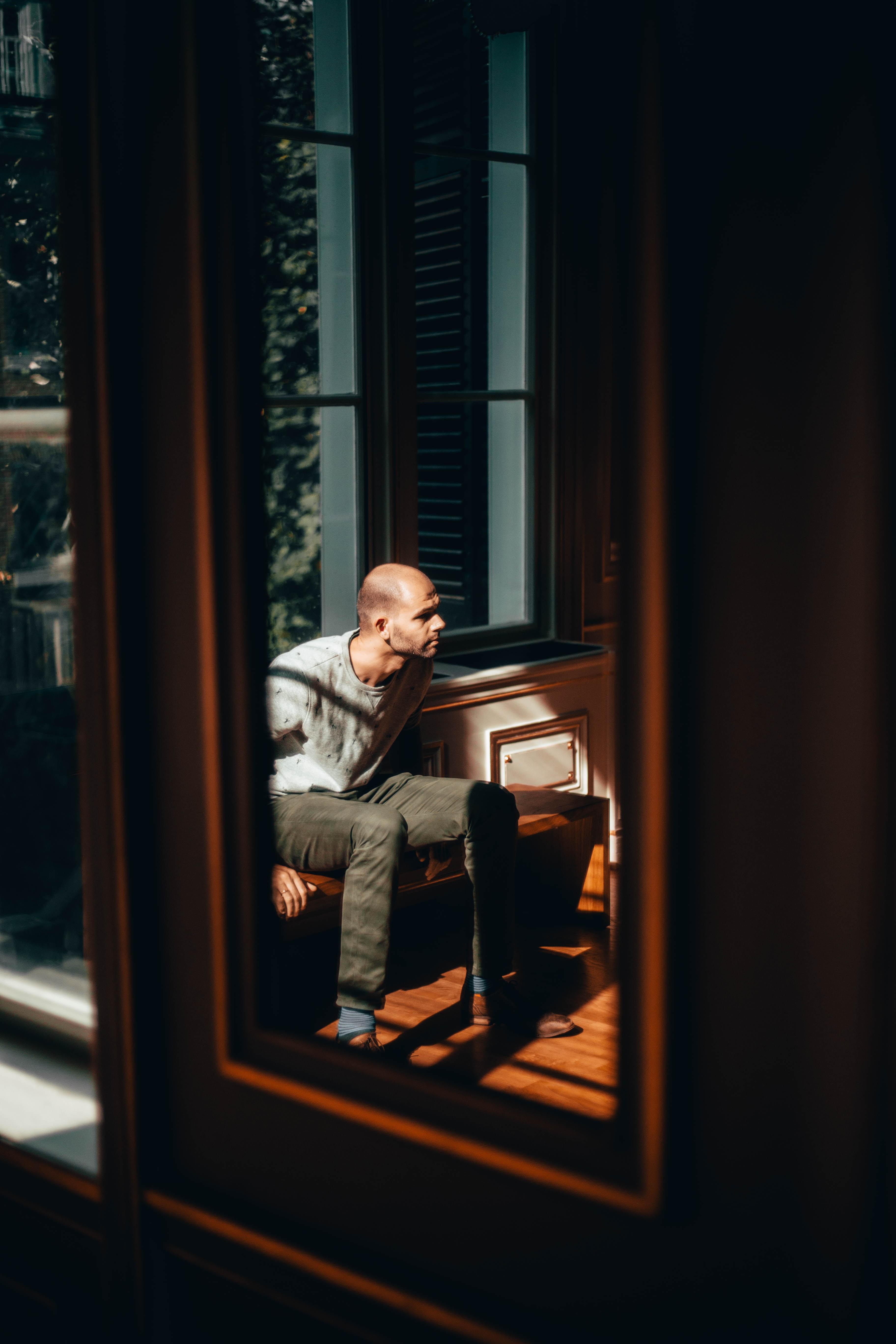 man sitting against window near mirror