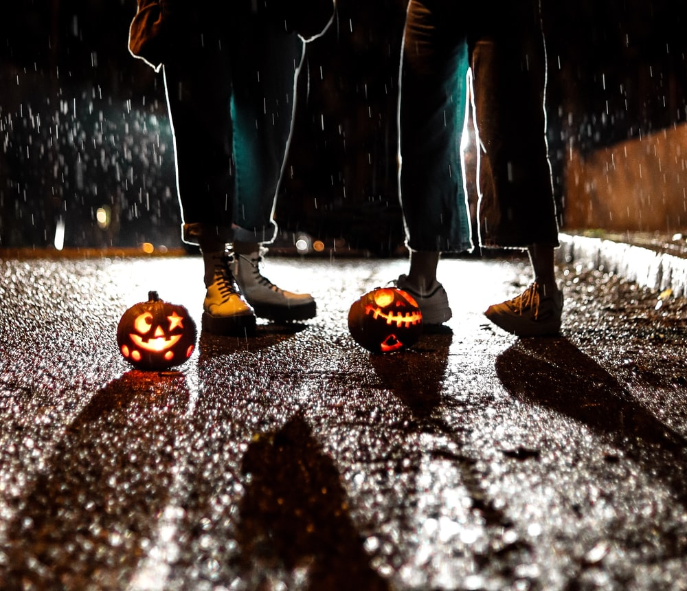 two people standing near Jack-O Lanterns