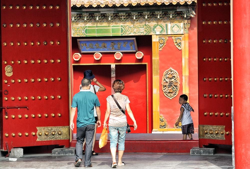 three people walking toward red building
