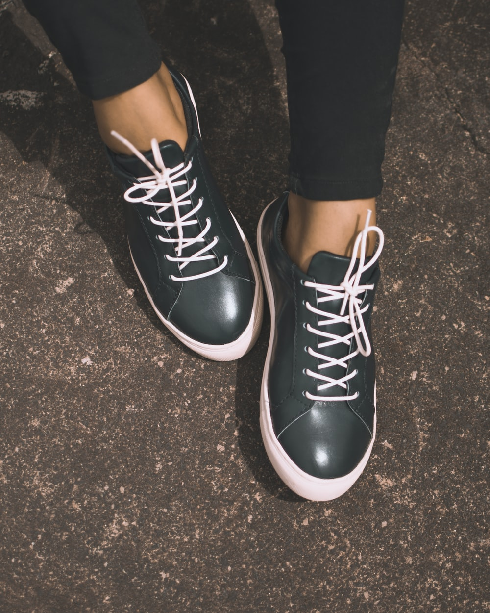person wearing black leather sneakers