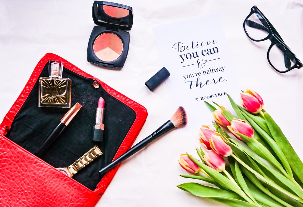 assorted cosmetics and pink tulip flowers