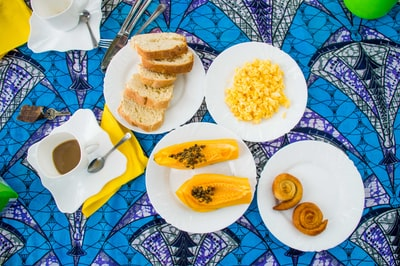 sliced papaya fruits, scramble egg, loaves of bread on white ceramic plates sao tome and principe zoom background