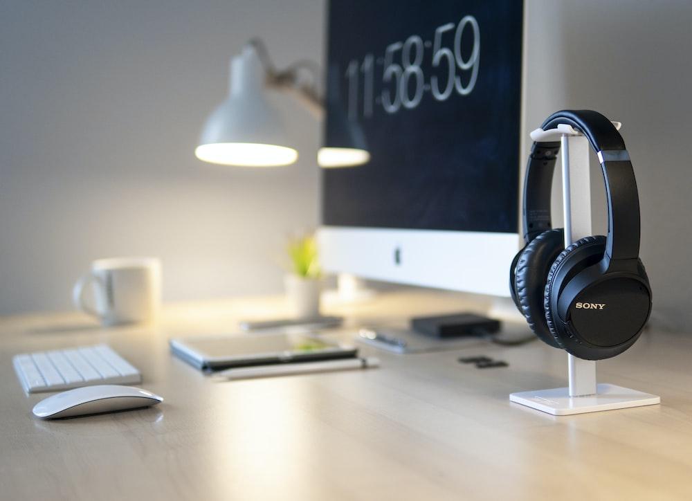 black Sony headphones beside iMac on top of table