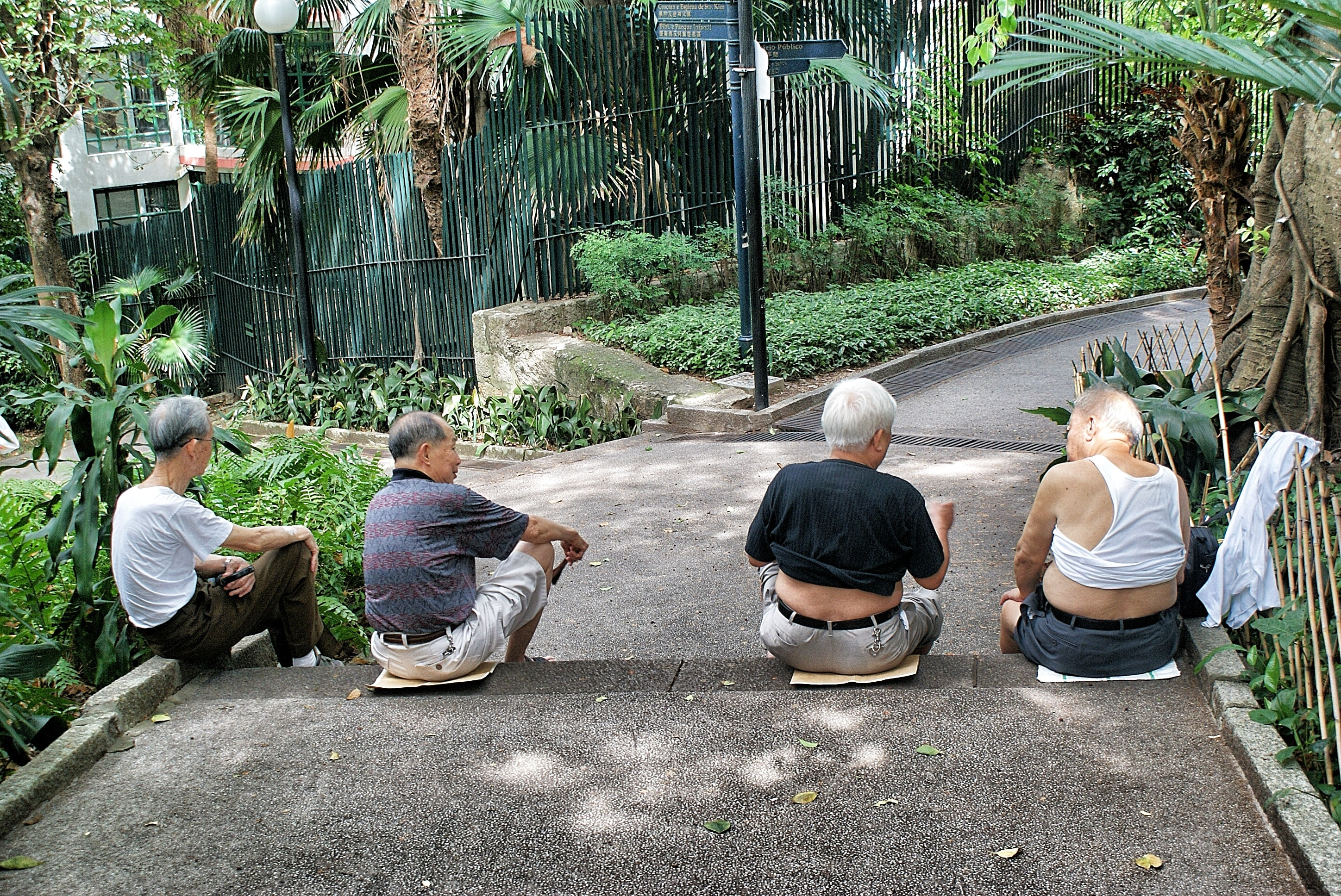 four persons sitting on gray surface