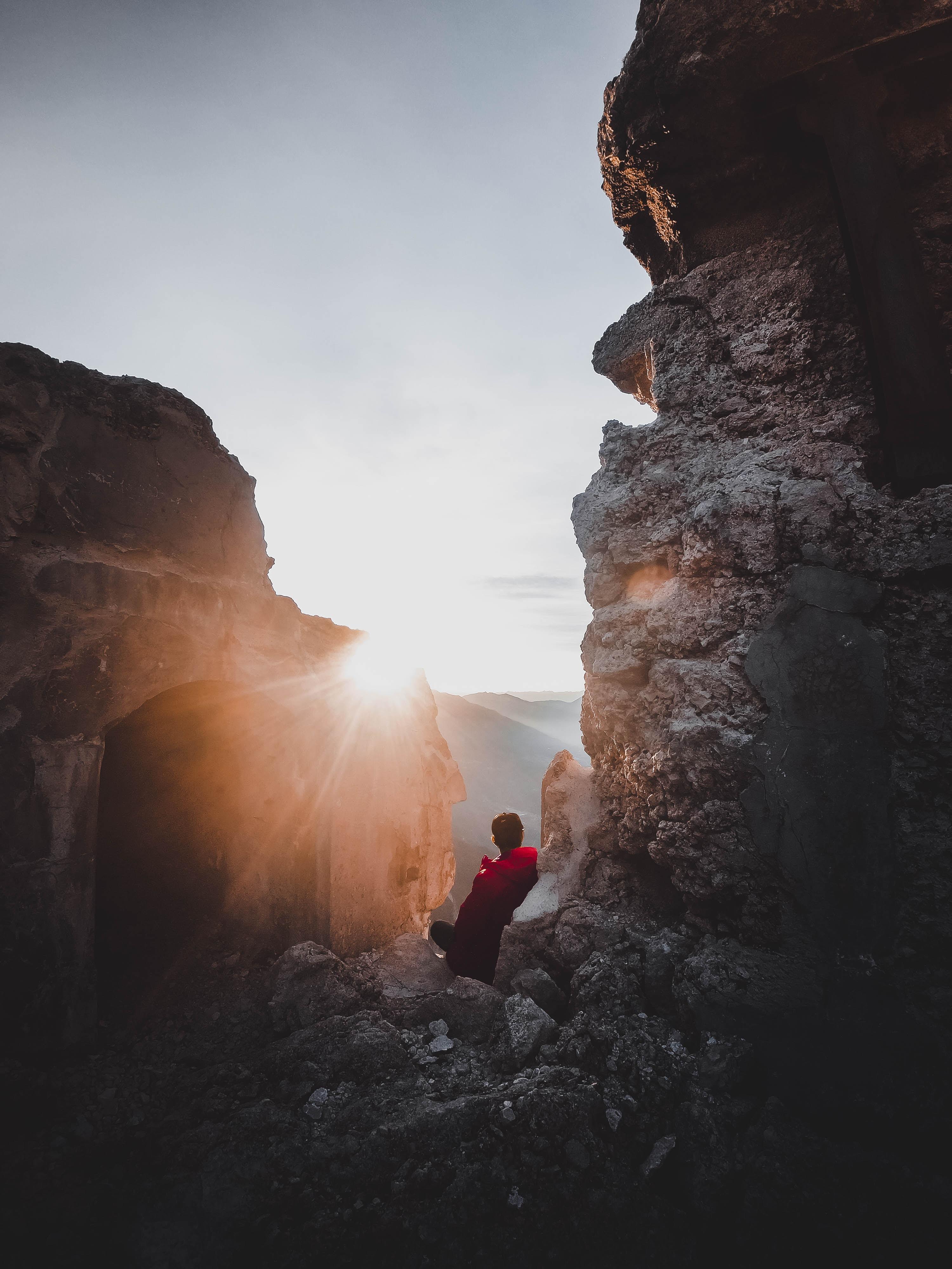 man sitting between rock formation during daytime