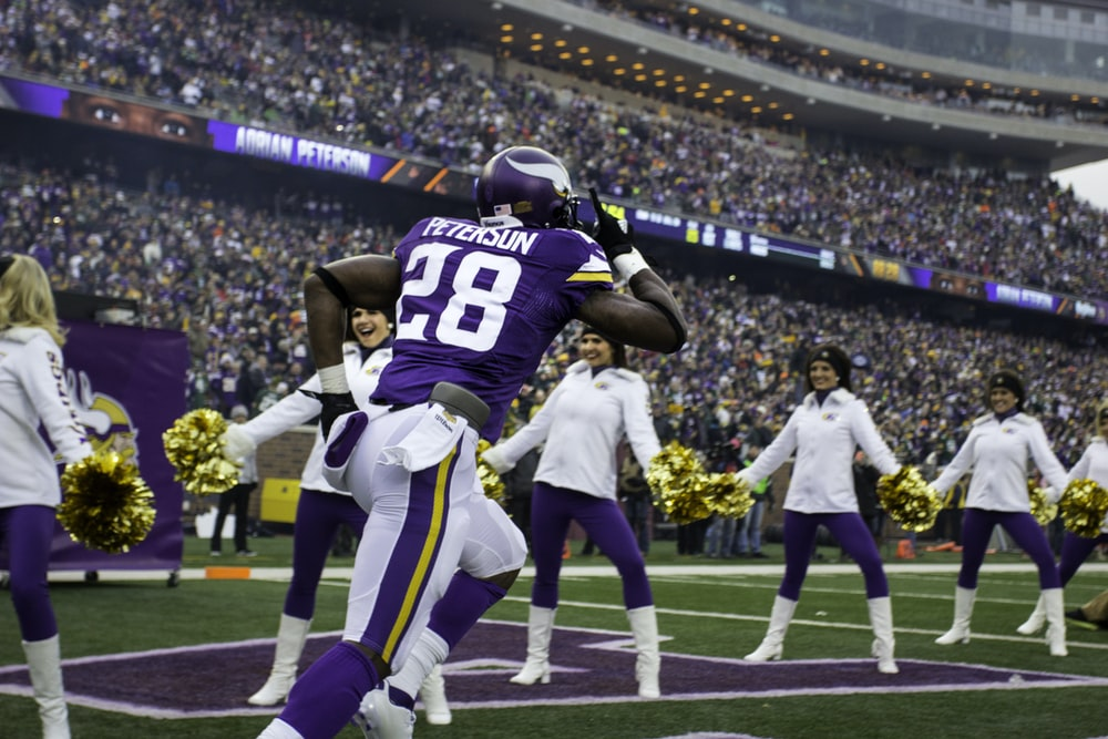 purple and white Peterson 28 running on stadium
