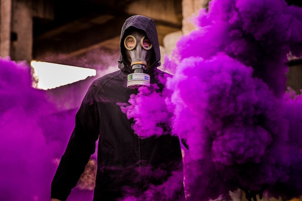 man wearing mask with purple smoke background