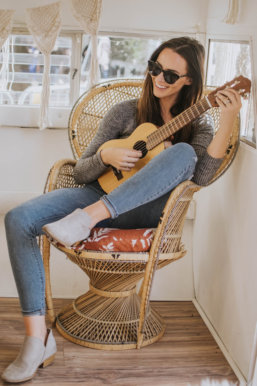 woman sitting on wicker chair holding classical guitar