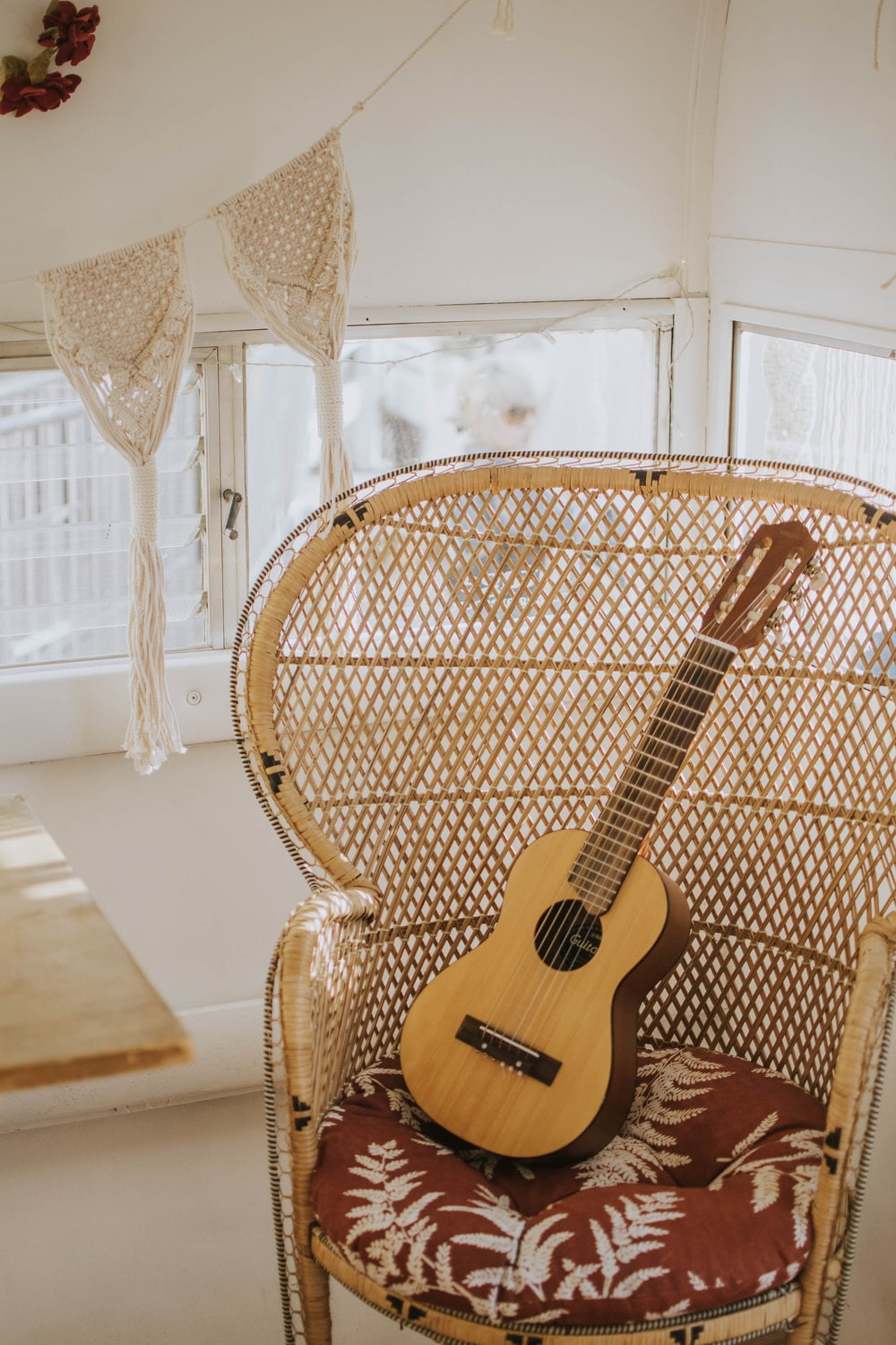 brown classical guitar on peacock chair
