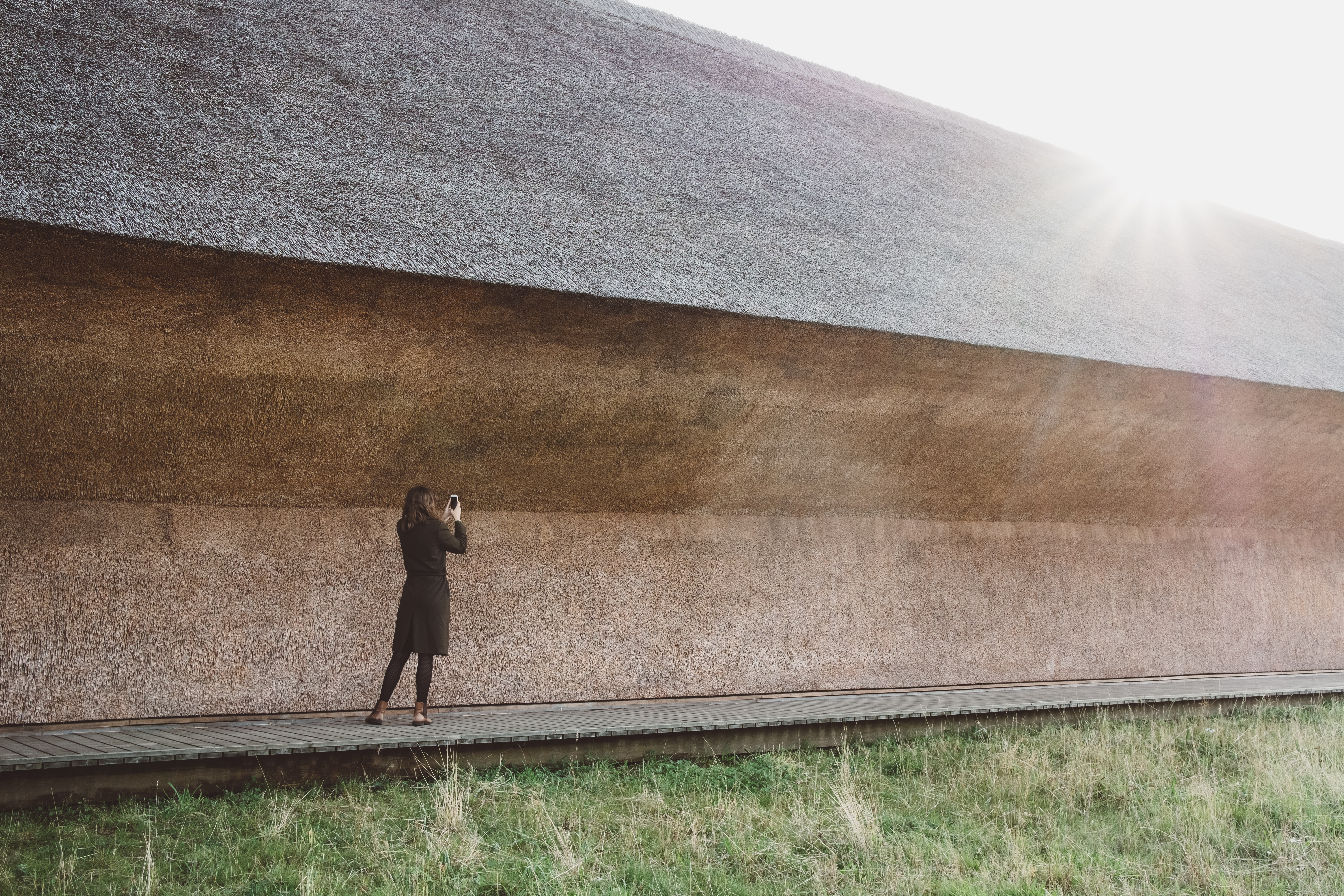 woman taking photo nearby grown concrete building