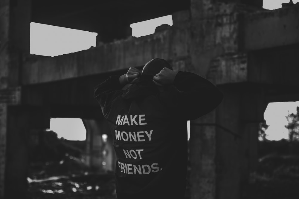 person wearing black and white make money not friends printed jacket