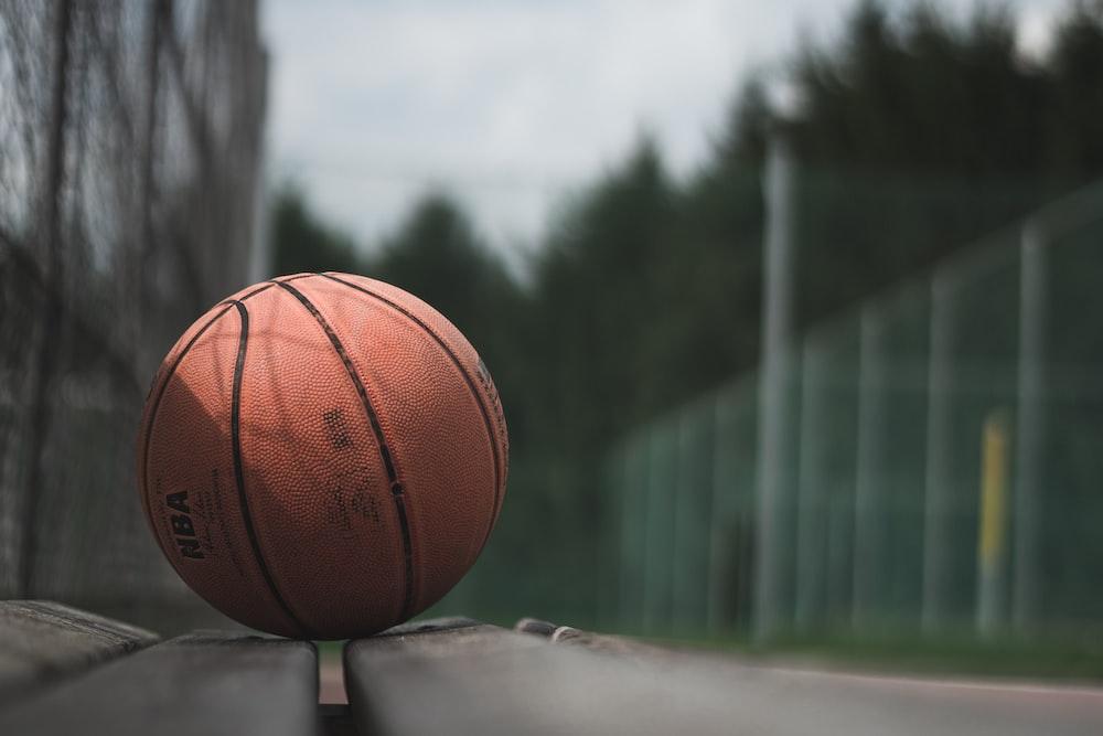 macro photography of brown NBA basketball ball on concrete surface