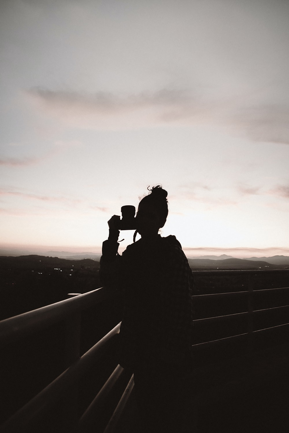 silhouette of person standing and holding camera