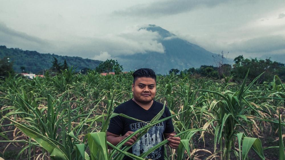 man standing on green grass field at daytime