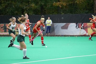women playing sport field hockey teams background