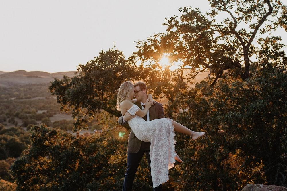 man carrying woman wearing white dress during sunrise
