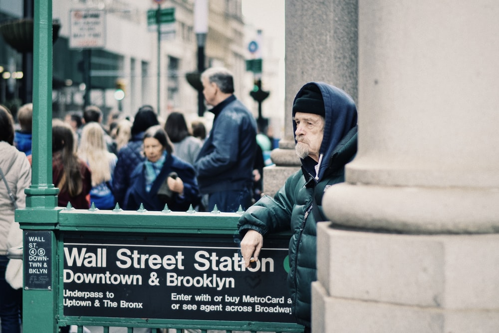 one unknown man standing beside wall street staton downtown and Brooklyn signboard