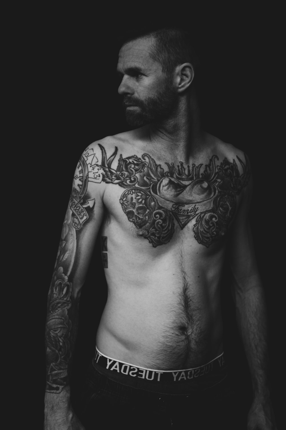 grayscale photography of topless man with tattoos