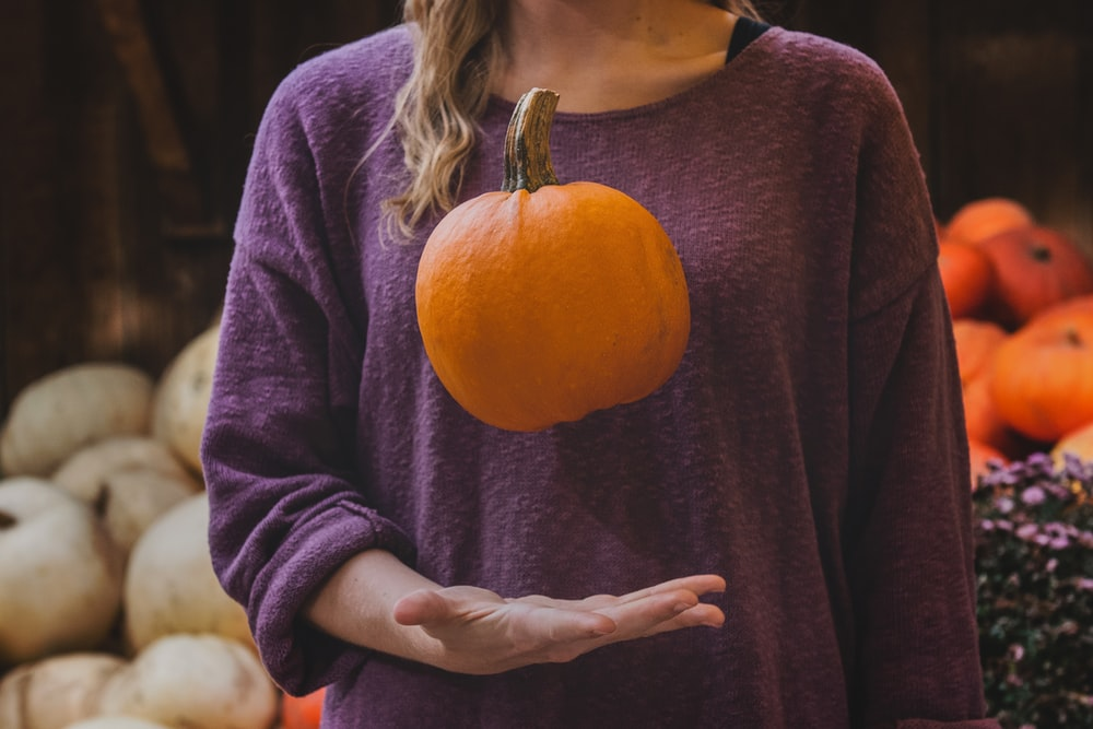 woman in purple shirt holding pumpkin