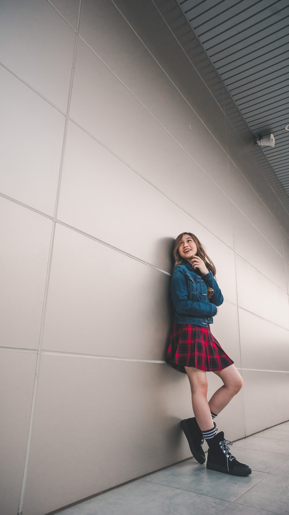 girl in blue jacket and red and black mini skirt leaning on wall
