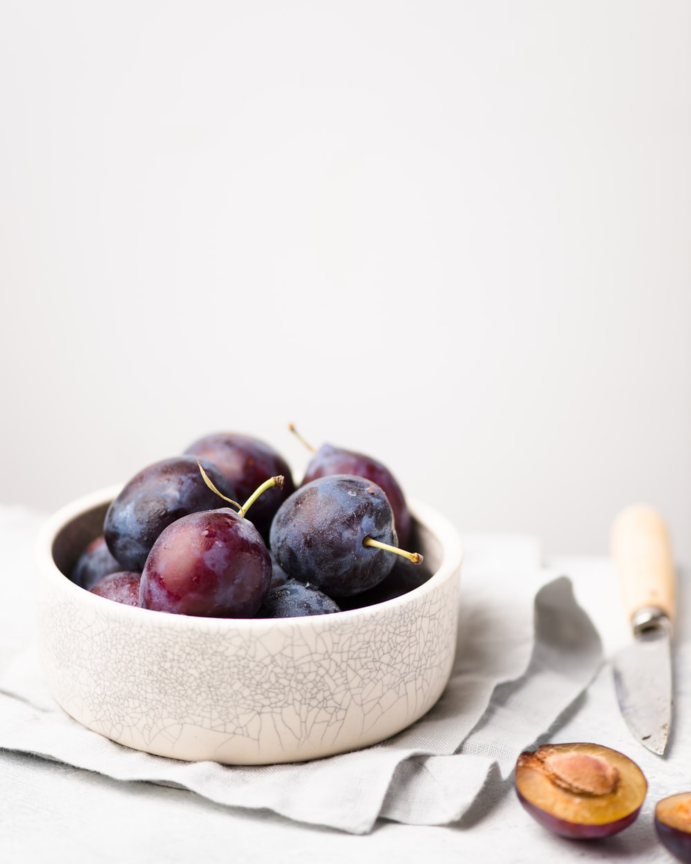 purple grapes on round white bowl