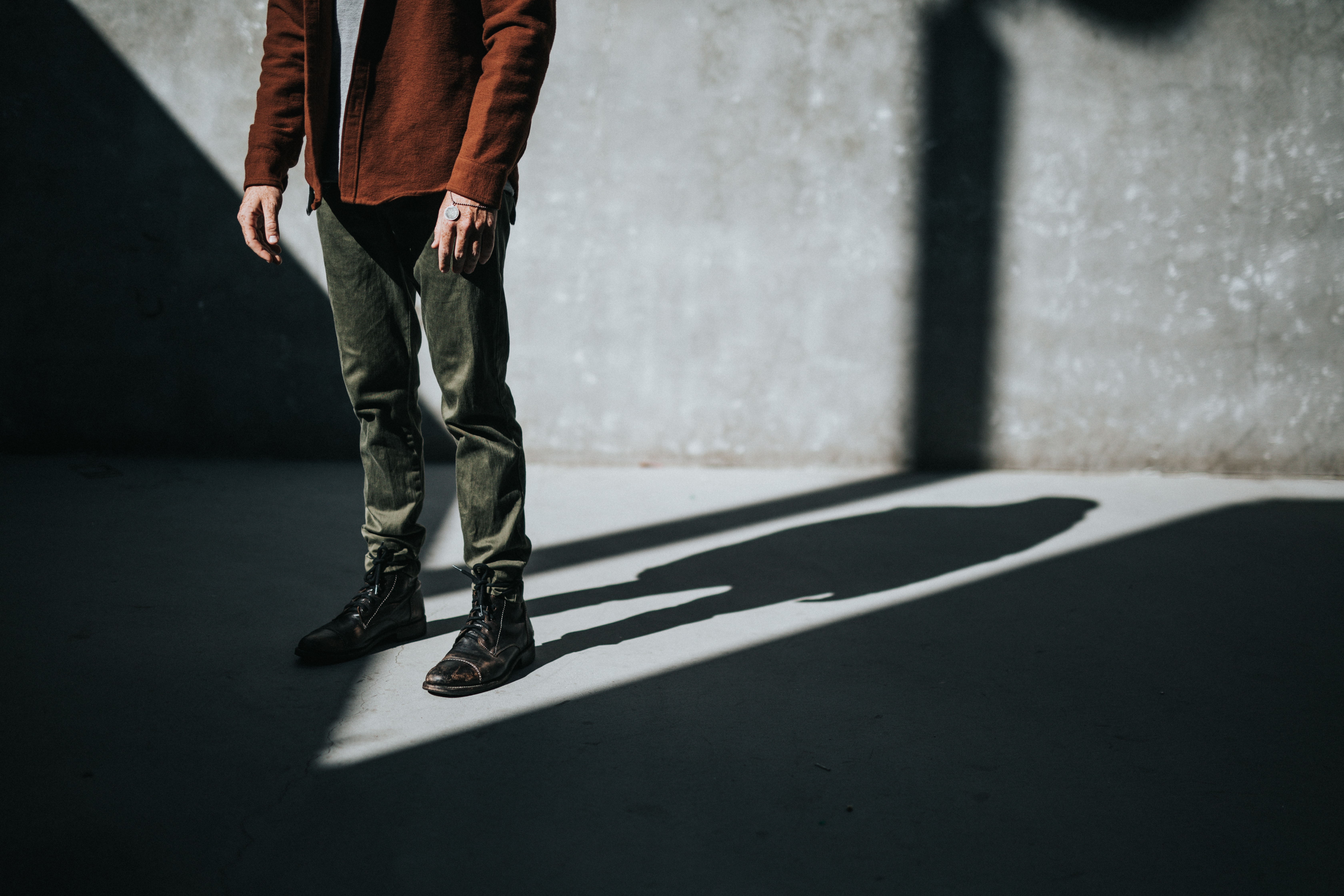 person standing near wall producing shadow
