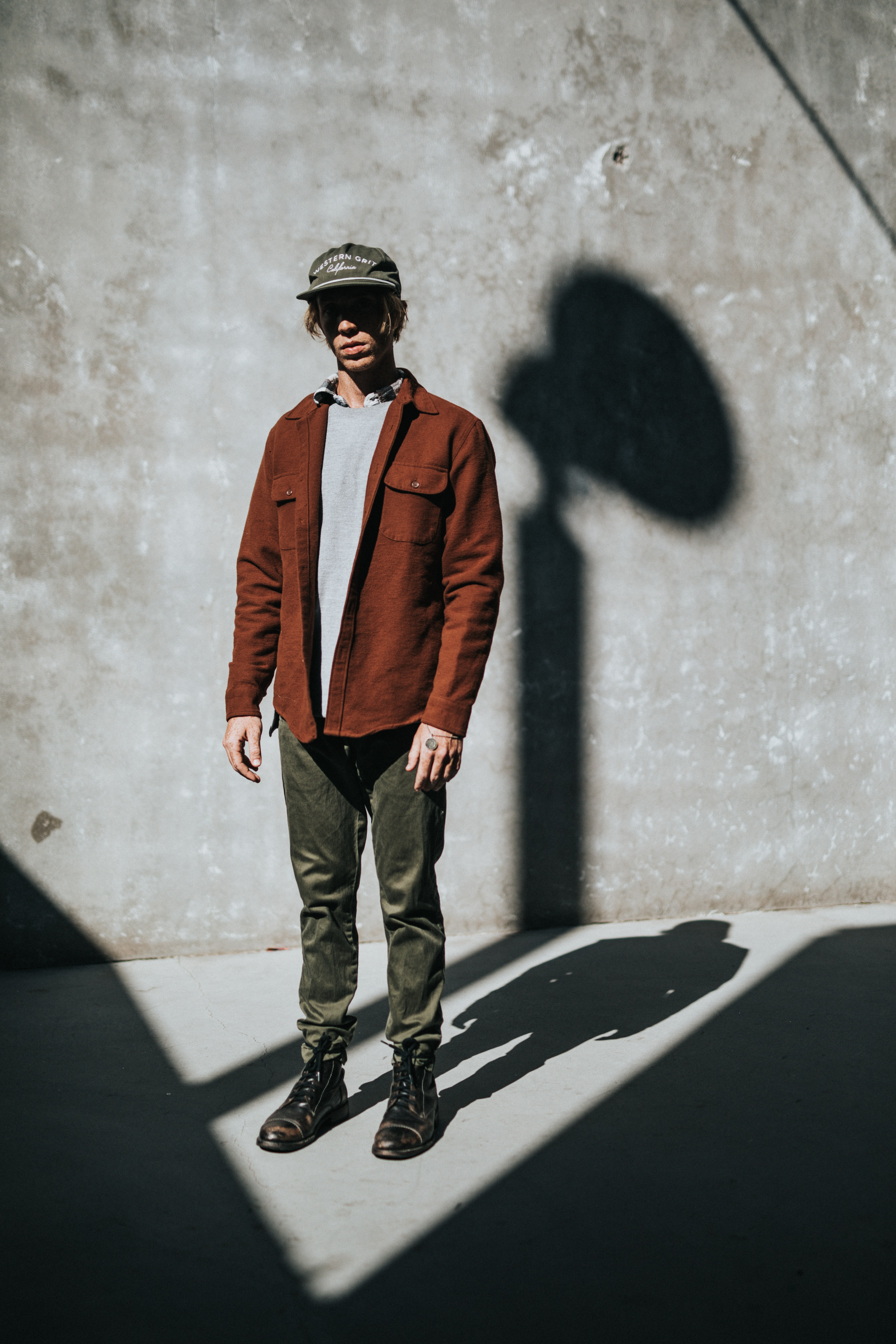 man stands near concrete wall with shadow