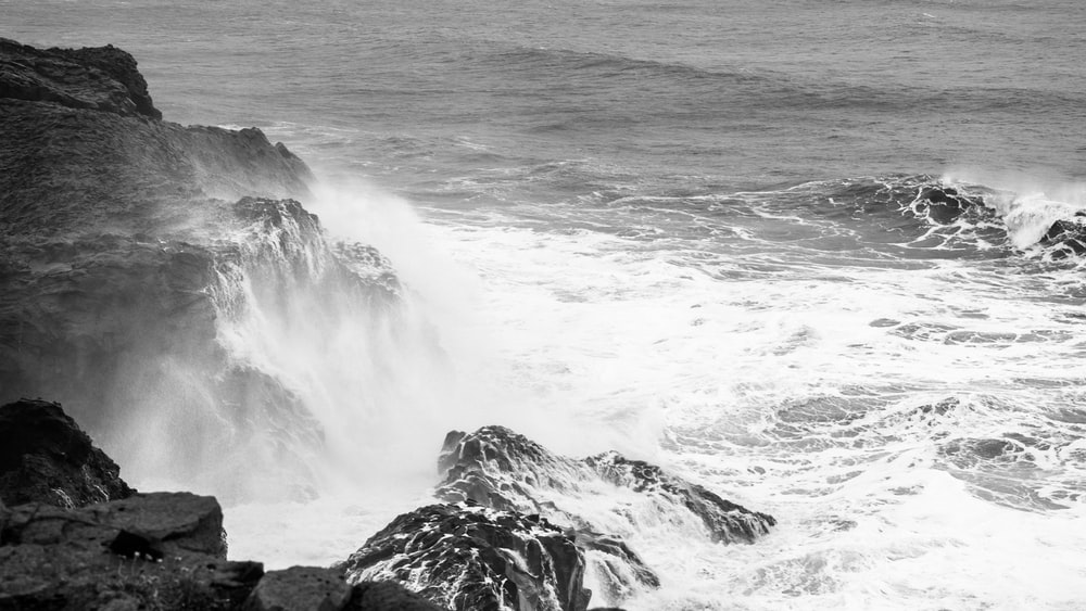 grayscale photography of sea water and rock formation