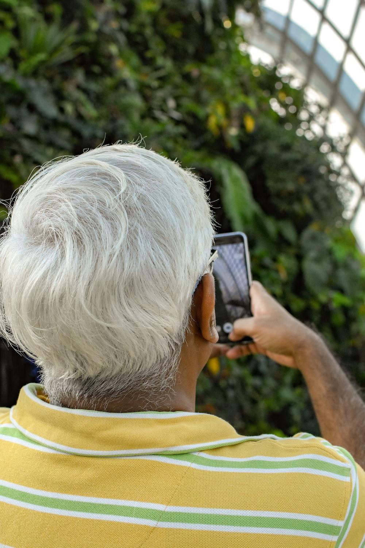 man holding smartphone near green plants