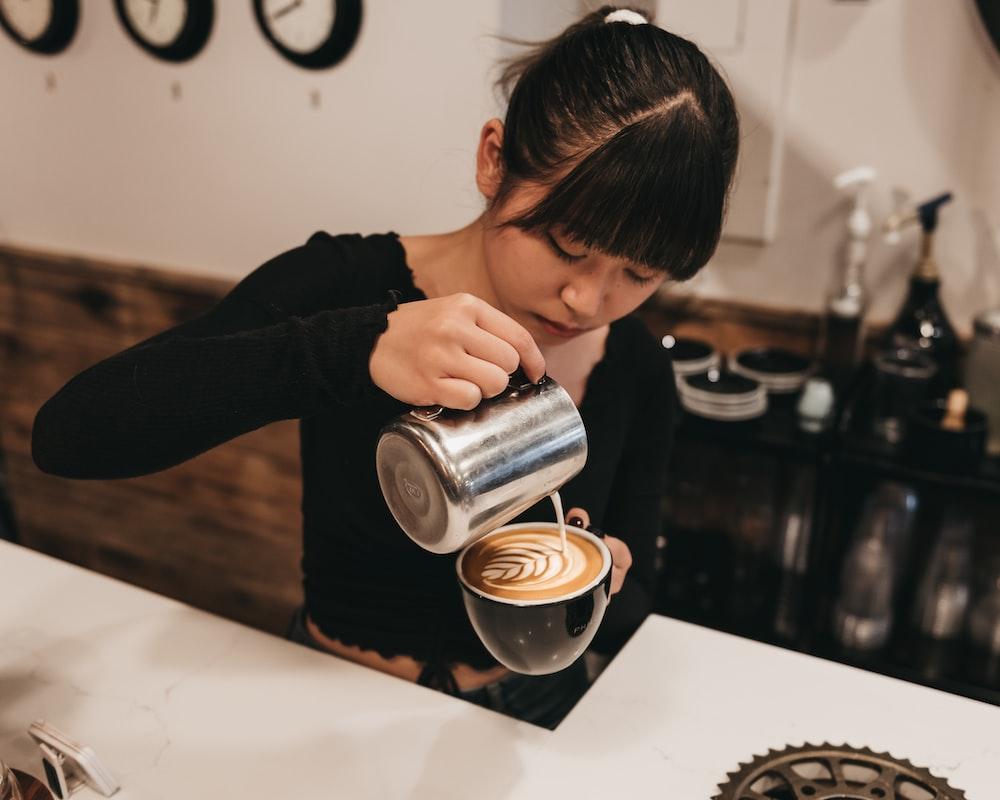 woman pouring cream on mug inside bar