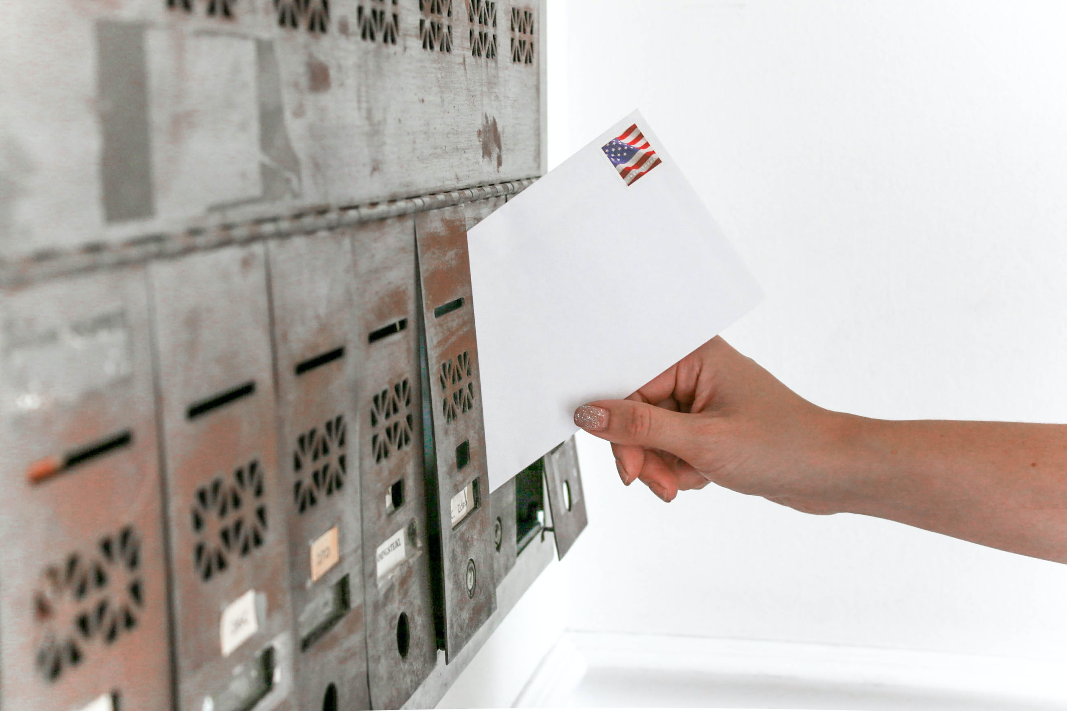 person holding mail envelope putting on box