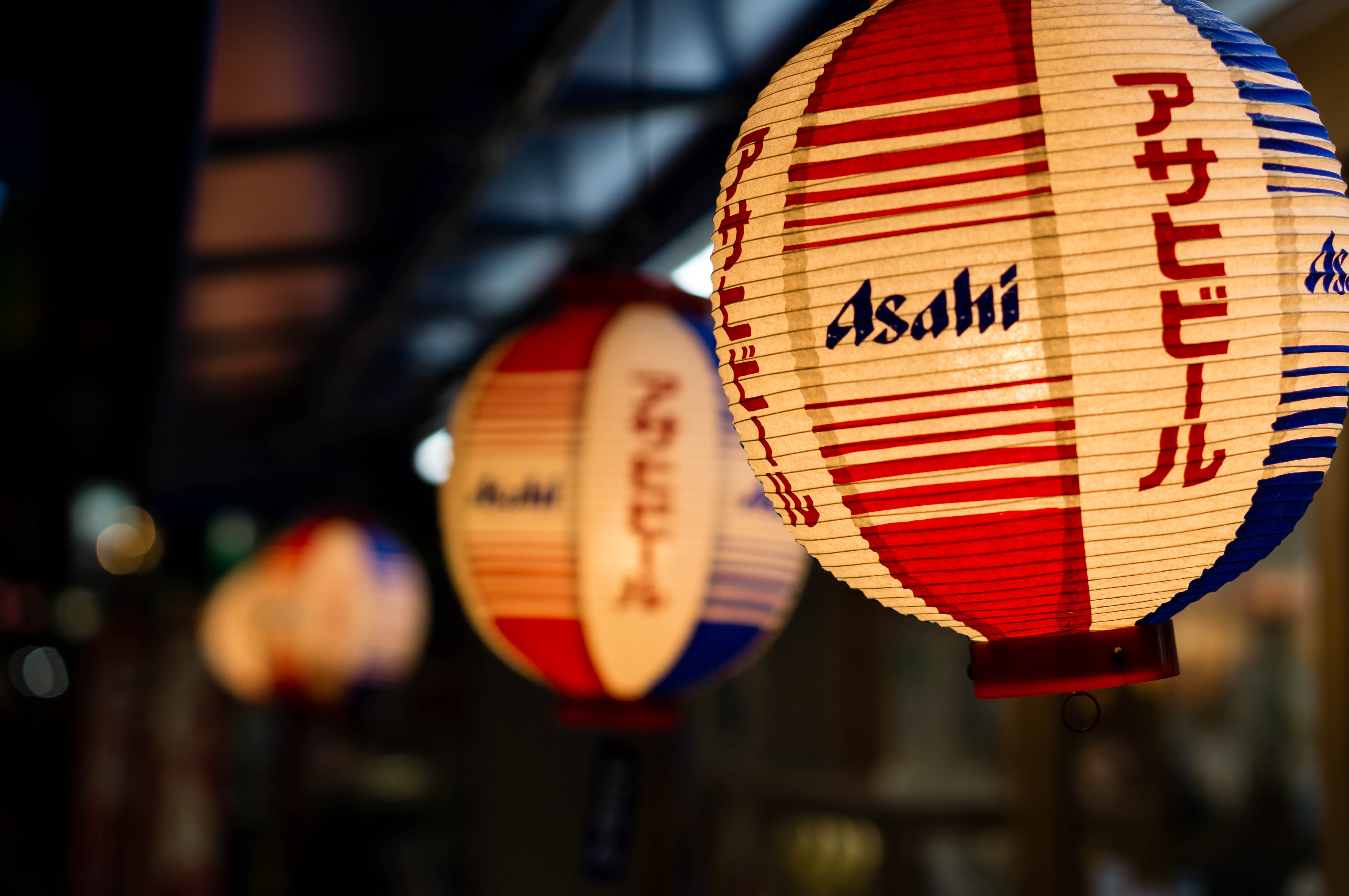 selective focus photography of white and red Asahi lantern