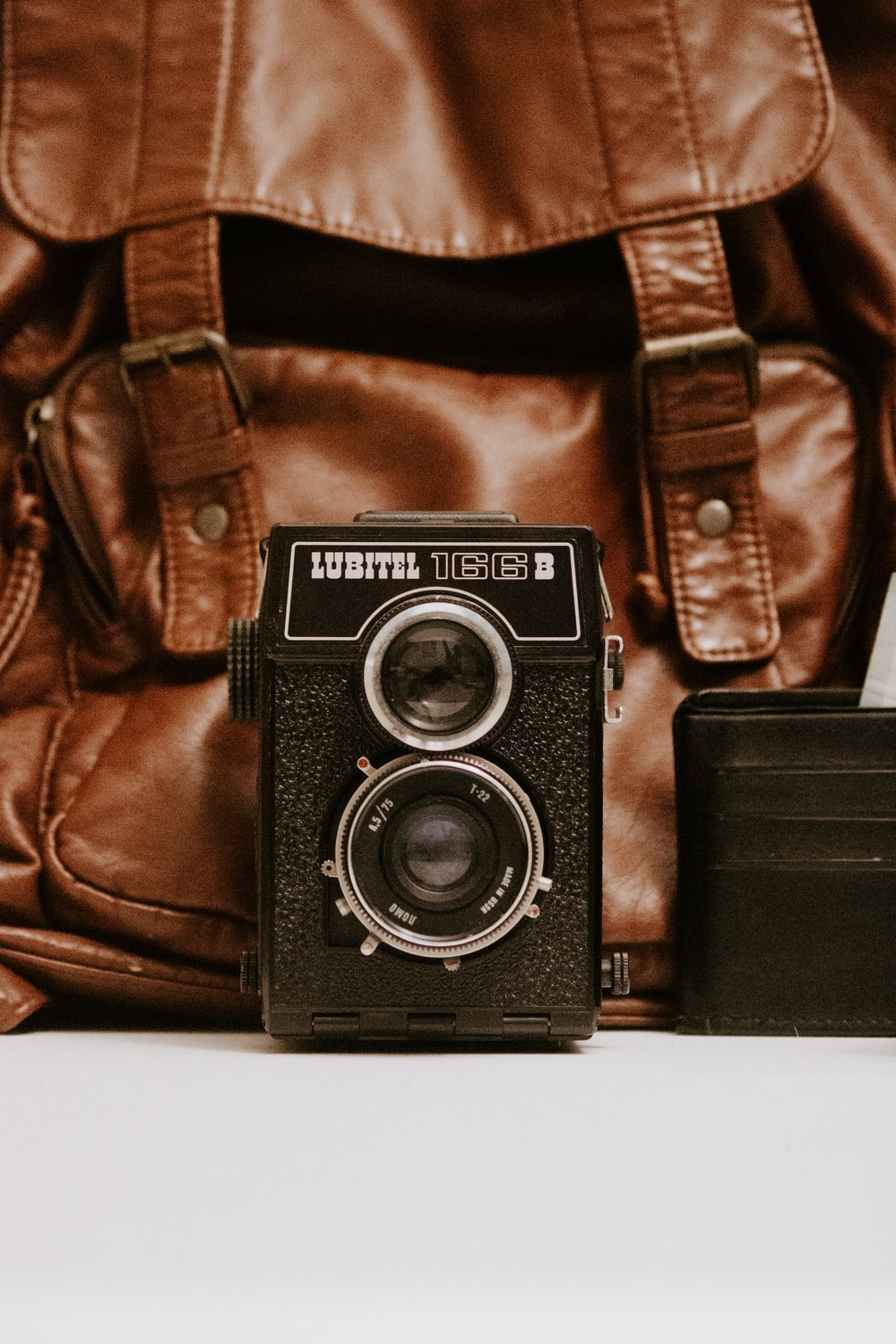 black Lubitel camera and brown leather bag