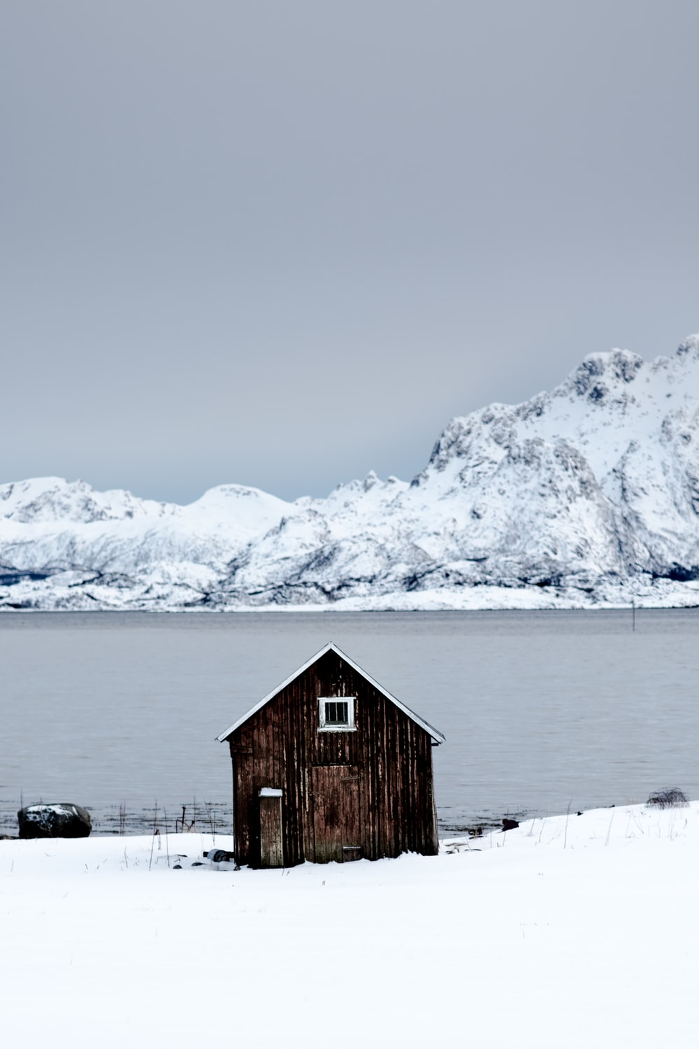 brown wooden shed near lake surrounded by snow